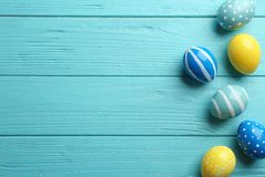 Flat lay composition of painted Easter eggs on wooden table. Space for text stock photo