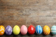 Flat lay composition of painted Easter eggs on wooden table. Space for text royalty free stock photos