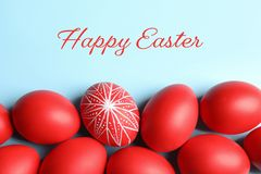 Flat lay composition of painted red Easter eggs on color background