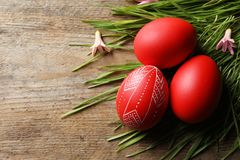 Flat lay composition of painted red Easter eggs and grass on wooden table, space for text. Flat lay composition of painted red Easter eggs and green grass on stock image