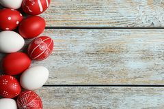Flat lay composition of painted red Easter eggs on wooden table. Space for text royalty free stock images