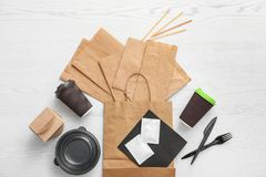 Flat lay composition with paper bags and different takeaway items on wooden background royalty free stock photo