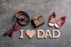 Flat lay composition with phrase I LOVE DAD small shoes and different gifts on grey background. Father`s day celebration. Flat lay composition with phrase I LOVE Royalty Free Stock Photos