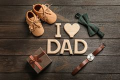 Flat lay composition with phrase. `I love dad`, small shoes and gift on wooden background. Father`s day celebration stock photos