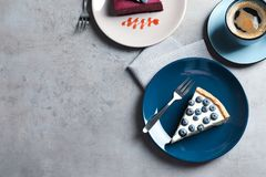 Flat lay composition with piece of tasty blueberry cake and space for text on table royalty free stock image