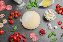 Flat lay composition with raw dough and ingredients. For pizza on grey background Royalty Free Stock Photos