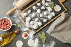 Flat lay composition with raw dumplings and ingredients on grey background. Process royalty free stock images