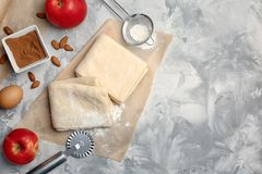 Flat lay composition with raw flaky dough. And ingredients on table Royalty Free Stock Photography