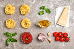 Flat lay composition with raw pasta and ingredients. For sauce on table Royalty Free Stock Photo