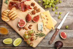 Flat lay composition with ripe figs and delicious products. On wooden background stock image