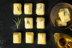 Flat lay composition with rosemary and olive oil ice cubes. On dark background royalty free stock image