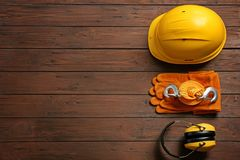 Flat lay composition with safety equipment and space for text. On wooden background royalty free stock photo