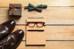 Flat lay composition with shoes, notebook. Tie and gift box on wooden background. Father`s day celebration Stock Photo