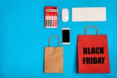 Flat lay composition with shopping bags. And text BLACK FRIDAY on color background. Sale and special offer royalty free stock photo