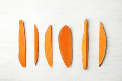 Flat lay composition with slices of sweet potato on white background. Flat lay composition with slices of sweet potato on white wooden background stock photos