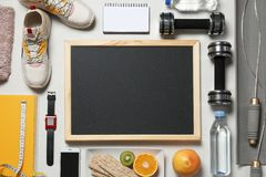 Flat lay composition with sport equipment and blackboard on gray background, space for text. Weight loss royalty free stock images
