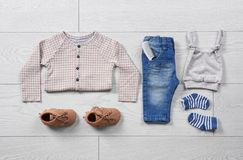 Flat lay composition with stylish child clothes. On wooden background royalty free stock images