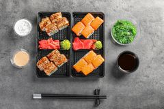Flat lay composition with sushi rolls on grey table. Food delivery royalty free stock photography