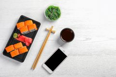Flat lay composition with sushi rolls, smartphone and space for text on white wooden table. Food delivery royalty free stock image