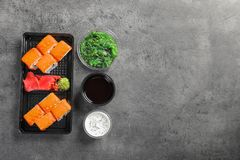 Flat lay composition with sushi rolls and space for text on grey table. Food delivery royalty free stock image