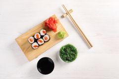 Flat lay composition with sushi rolls on white wooden table. Food delivery royalty free stock photos