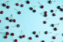 Flat lay composition with sweet red cherries. On color background stock image