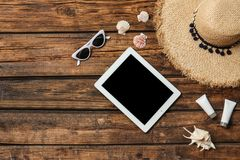 Flat lay composition with tablet and beach objects. On wooden background royalty free stock photography