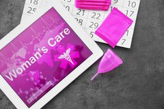 Flat lay composition with tablet, calendar. And feminine hygiene items on grey background. Gynecological care stock photo