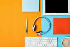 Flat lay composition with tablet, computer keyboard, headphones and space for text. On color background stock photography