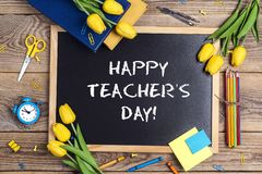 Flat lay composition for Teacher`s day on chalkboard with school supplies and tulip flowers on a rustic wooden table