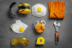 Flat lay composition with tools and safety equipment on grey. Background royalty free stock images