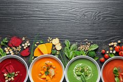 Flat lay composition with various soups, ingredients and space for text on wooden background stock images