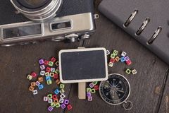 Flat lay composition of vintage camera,compass, planner book and word block on wooden table Royalty Free Stock Image