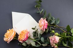 Flat lay composition with a white envelope, blank card and a peony rose flower on a grey background royalty free stock photo