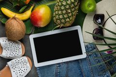 Free Flat Lay Composition With Tropical Fruits Pineapple Mango Bananas Coconut On Large Palm Leaf. Women Jeans Shorts Slippers Hat Royalty Free Stock Image - 110792916