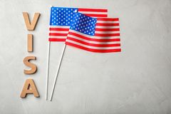 Flat lay composition with word VISA. And flags of USA on gray background. Space for text royalty free stock photography