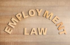 Flat lay composition with phrase EMPLOYMENT LAW on wooden background stock images