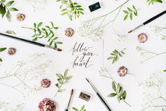 Flat lay composition, workspace with quote follow your heart written in calligraphy style Royalty Free Stock Photography