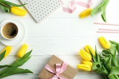 Flat lay composition with yellow tulip flowers and gift box on wooden background stock photo