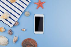 Flat lay concept of summer travel vacations. Creative flat lay concept of summer travel vacations. Top view of beach towel, seashells, starfish and smartphone on stock photography