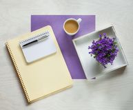 Flat lay concept with writing pad, pen and beautiful violet flowers Stock Image