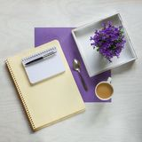 Flat lay concept with writing pad, pen and beautiful violet flowers Stock Photos