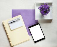 Flat lay concept with writing pad, pen and beautiful violet flowers Royalty Free Stock Photography