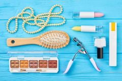 Flat lay cosmetics and accessories. Women makeup products and equipment, blue wooden background. Femininity and fashion concept Royalty Free Stock Images