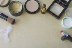 Flat lay of cosmetics set for make-up on brown paper. Face powder, lipstick, brush, loose powder Stock Photos