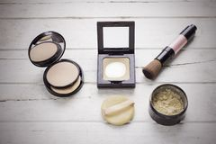 Flat lay of cosmetics set for make up. Press powder, brush and loose powder on white wooden desk with vintage filter Royalty Free Stock Image