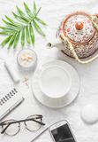 Flat lay cozy morning inspiration planning female table - teapot, tea cup, notepad, glasses, phone, lipstick, face cream, green le. Af flower on light background Royalty Free Stock Photos