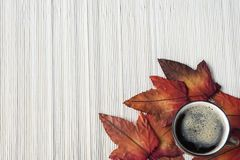 Flat lay cup of coffee with autumn leaves against bamboo background royalty free stock image