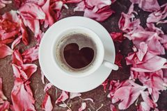 Flat lay cup of coffee with heart shape pattern surrounded with light pink peony flower petals on black stone background. royalty free stock photos