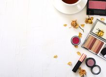 Flat lay with cup of tea and woman make up products stock photos